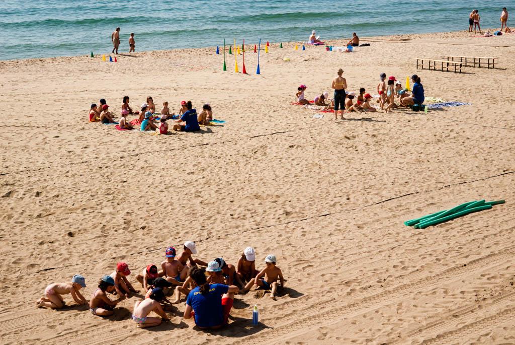 Beach of Barcelona, Spain. Children, schools, toursits playing