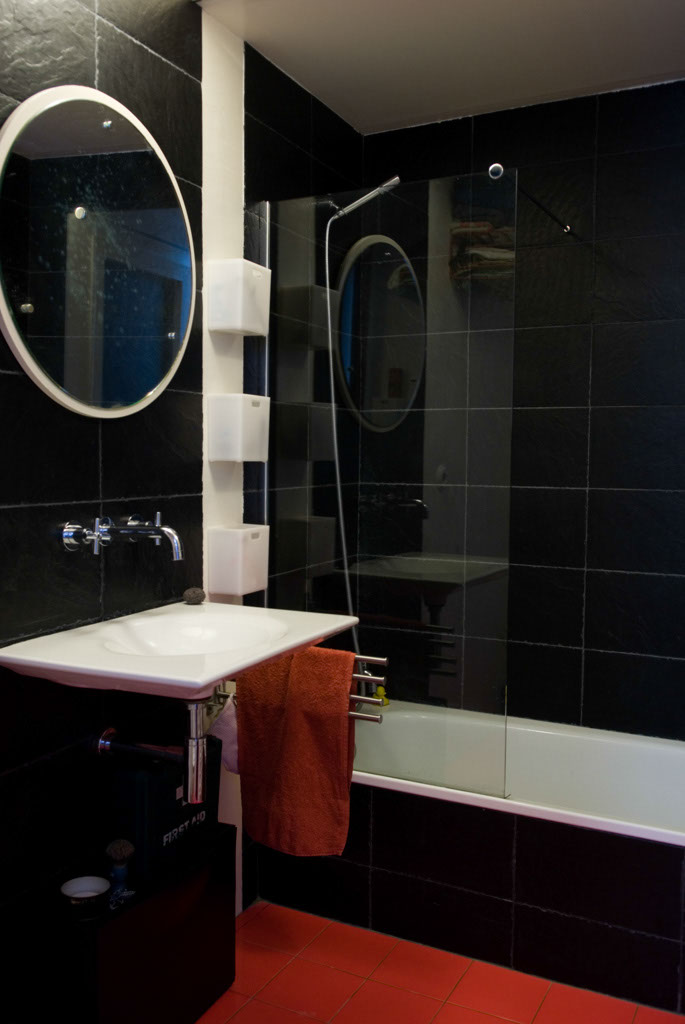 R3project bathroom. Slate imitating tiles made from recycled plastic, Kalahari sink by Roca, second hand mirror, recyclable glass shower, reused bathtub, locally sourced red tiles by TAU, low-flow tap by Roca