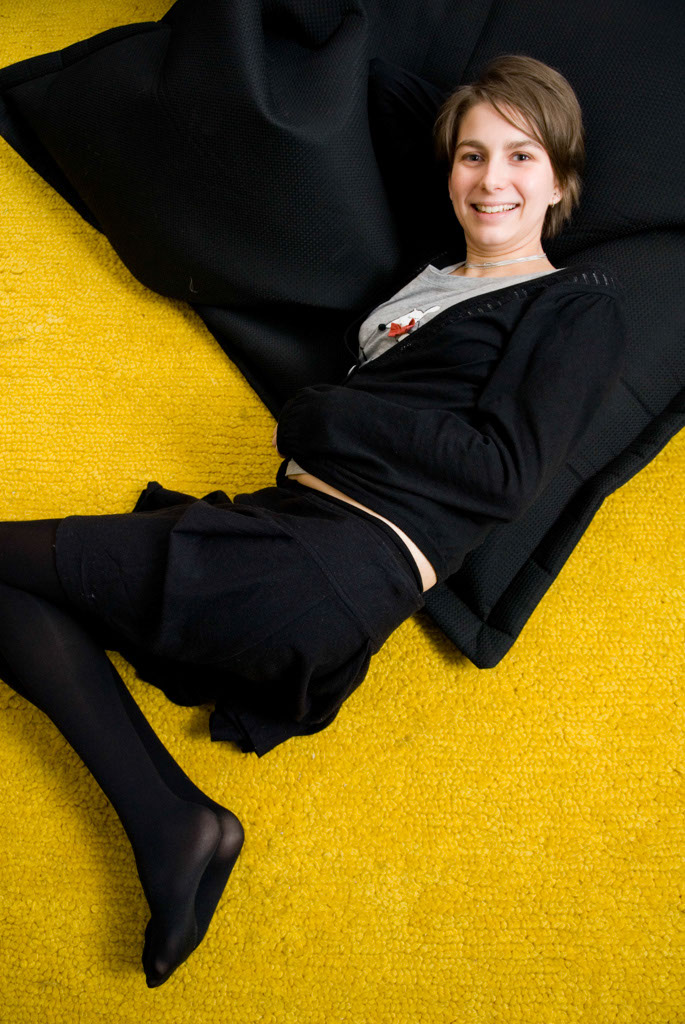 Petz Scholtus on recycled pouf by WASTE and yellow eco-ethical rug by Nani Marquina